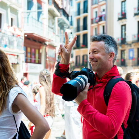 hemingway: Photographer on San Fermin. Photojournalist. People celebrate San Fermin festival in traditional white and red clothing with red necktie
