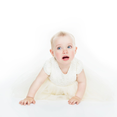 Little Princess in white dress crawls in studio over white background