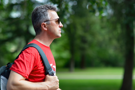 Portrait of handsome middle-aged man in profile in summer park. Stock Photo