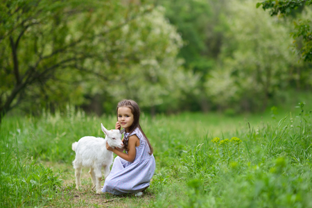 Cute kid with baby animal, countryside outdoor portrait