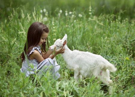 Little girl plays and huhs goatling in country, spring or summer nature outdoor. Cute kid with baby animal, countryside outdoor portrait, forest, trod, glade background. Stock Photo