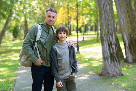 Portrait of father with his son walking together in autumn park. Stock Photo