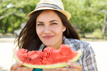 Happy young woman eating watermelon