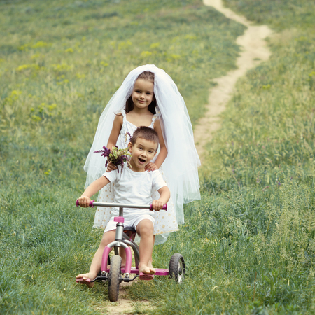 Young bride and groom playing wedding summer outdoor. Children like newlyweds on bicycle.