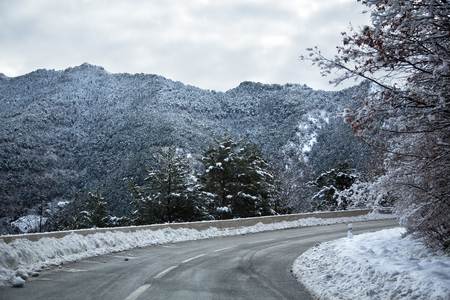 Vivid landscape with road, winter mountain and cloudy sky. Stock Photo
