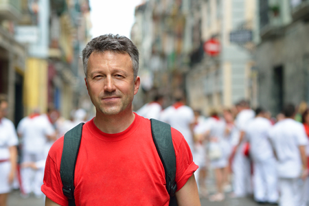 Man in celebrating San Fermin festival in traditional white and red clothing with red in Pamplona, Navarra, Spain. Stock Photo