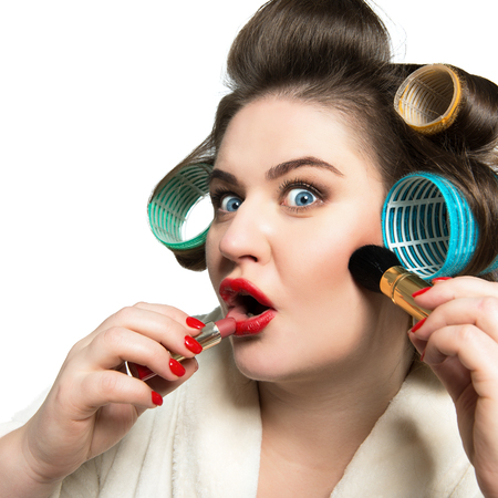 Funny portrait of blue-eyed woman in curlers does makeup and looking at camera like in the mirror over white background.