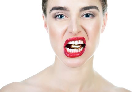 Blue-eyed girl with red lipstick holding bullet in her teeth. Stock Photo
