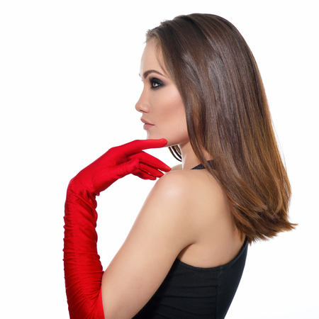 Fashionable woman. Beautiful female face in profile. Woman of high society. Heartbreaker. Beauty woman. Portrait of amazing young fashion woman posing at studio in red gloves and black dress over white background.