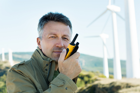 Man talking with portable radio transmitter outdoor over the wind turbines, image toned. 版權商用圖片