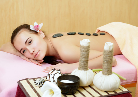 Body care. Beautiful young woman relaxing with stones on her back at beauty spa salon.