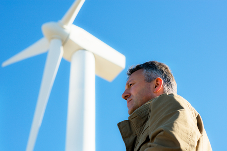 Mans portrait outdoor against blue sky with wind turbine Stock Photo