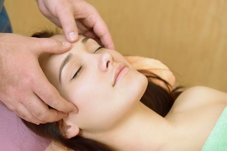 Body care. Face massage. Beautiful young woman relaxing with hand massage at beauty spa salon. Stock Photo