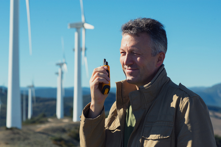 Man talking with portable radio transmitter outdoor over the wind turbines, image toned. Windmill generators. Wind power generators. Reklamní fotografie