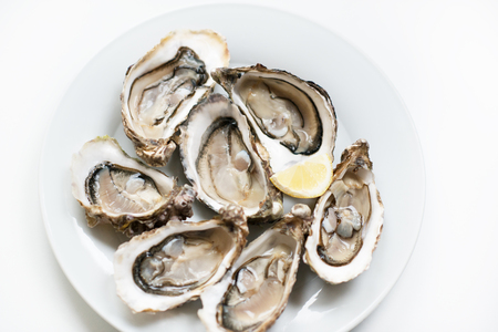 Fresh oysters. Raw fresh oysters are on white round plate, image isolated, with soft focus. Restaurant delicacy. Fresh raw oysters. Saltwater oysters. Stock Photo