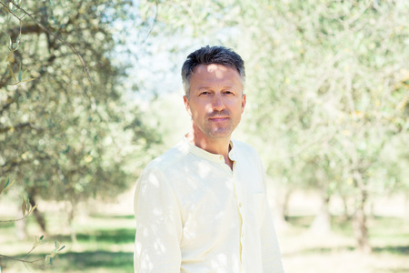 Olive trees. Handsome man posing in olive trees garden. Male portrain over mediterranean olive field ready for harvest. Confident mature man in italian olive's grove with ripe fresh olives. Fresh olives. Olive farm Фото со стока