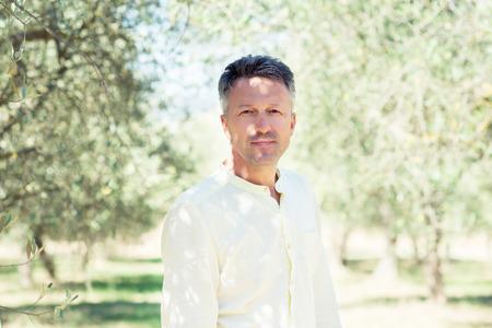 Olivenbäume. Hübscher Mann, der im Garten der Olivenbäume aufwirft. Männlicher Portrain über mediterranem Olivenfeld bereit zur Ernte. Selbstbewusster reifer Mann im italienischen Olivenhain mit reifen frischen Oliven. Frische Oliven. Olivenfarm