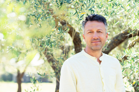 Olive trees. Handsome man posing in olive trees garden. Male portrain over mediterranean olive field ready for harvest. Confident mature man in italian olive's grove with ripe fresh olives. Fresh olives. Olive farm