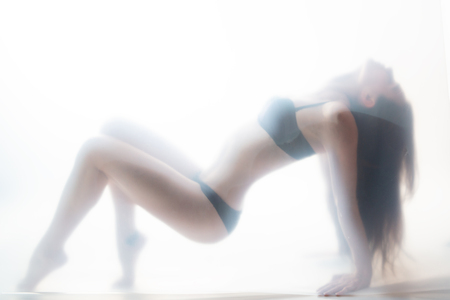 Young beautiful woman posing in lingerie behind translucent material. Full-length attractive sexy girls portrait in studio over white background, foggy silhouette. Art female portrait.