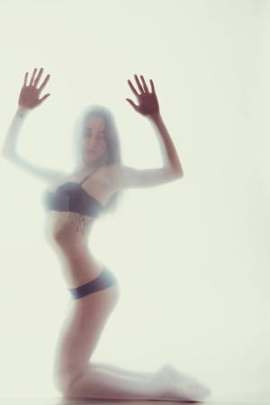Young beautiful woman posing in lingerie behind translucent material. Full-length attractive sexy girls portrait in studio over white background, foggy silhouette. Art female portrait, image toned.