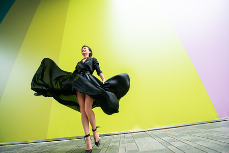 Fashion woman. Young beautiful chinese girl dancing outdoor wearing long black dress with high heels over colorful wall background. Stylish trendy lady. 写真素材