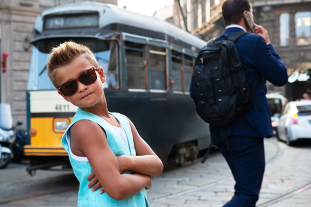 Young boy posing in the milanese street with old tram on background. Cute happy 6 years old boy posing in Milan, Italy. Kid's street fashion. Trendy boy in suit walking in the Italian capital of fashion. Foto de archivo - 111665570