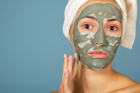 Beautiful cheerful teen girl applying facial clay mask. Beauty treatments, isolated on blue background. 免版税图像