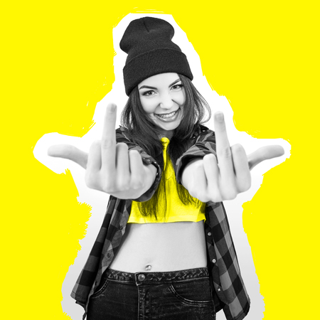 Hipster girl in jeans, checked shirt and hat showing middle fingers over yellow background. Impertinent behaviour. Hipsters. Provocation. Aggression. Naughtiness. Modern high fashion look