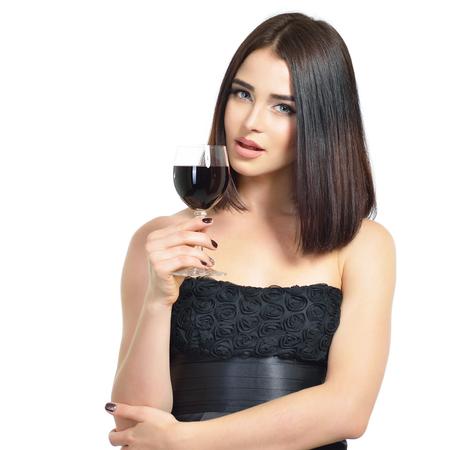 Giovane donna attraente che tiene un bicchiere di vino rosso. La bella signora beve una bevanda alcolica