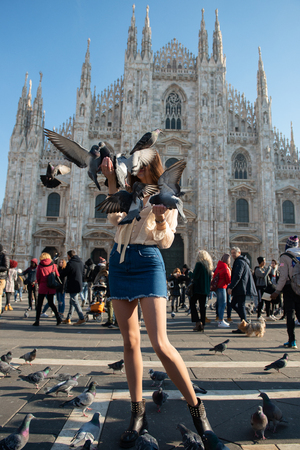 Young attractive woman posing with pigeon near Milan Cathedral (Duomo di Milano), Italy.