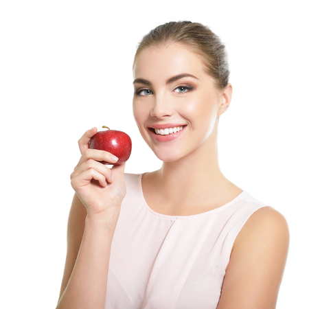 Beauty female portrait. Young attractive woman posing at studio with apple over white background. Beautiful girl with perfect smile. Model with perfect make-up