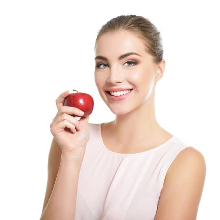 Piękno portret kobiety. Młoda atrakcyjna kobieta pozuje w studio z jabłkiem na białym tle. Piękna dziewczyna z idealnym uśmiechem. Model z perfekcyjnym makijażem