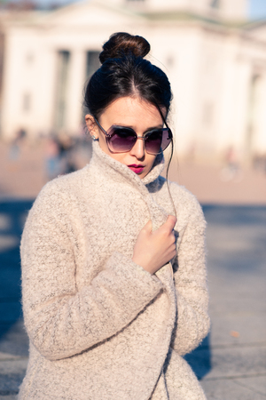 Attractive young woman wearing gray coat with long dark hair and sun glasses posing outdoor in Milan streets, Italy. Beautiful caucasian model portrait. Street fashion Stock Photo