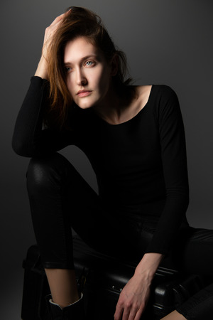 Fashion model. Young woman posing in studio wearing black with boots. Beautiful caucasian girl over gray background Stock Photo - 123014075