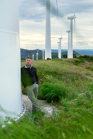 Handsome man. Outdoor male portrait over landscape with wind turbines. Image toned.