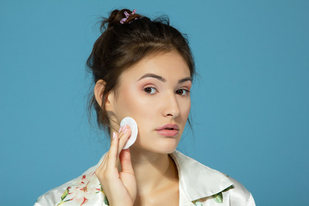 Cheer attractive teen girl clean her face with cotton disk. Morning theme. Over blue background. Stock Photo