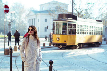 Attractive young woman wearing gray coat with long dark hair and sun glasses posing outdoor in Milan streets, Italy. Beautiful caucasian model portrait.