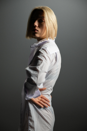 Fashion model. Young blond woman posing in studio wearing white shirt. Beautiful caucasian girl over gray background Stock Photo - 123014147