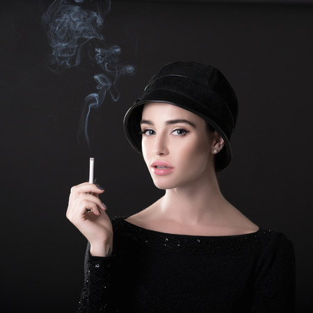 Young fashion woman smoking cigarette in hat and black drees over dark background. Vintage female portrait, styling. Image toned.