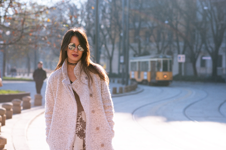 Attractive young woman wearing gray coat with long dark hair and sun glasses posing outdoor in Milan streets, Italy. Beautiful caucasian model portrait. Stock Photo - 122781837