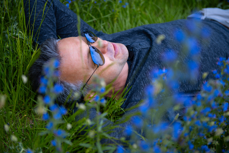 Portrait of handsome middle-aged man lying on field among blue flowers. Pensive calm man over nature outdoor. Closeup male face in green grass, image toned.
