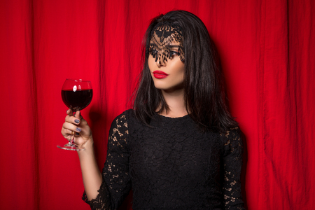 Young beautiful woman holding glass of wine over red curtains Stock Photo