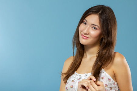 Portrait of cute morning girl. Beautiful cheerful teen girl looking at camera over blue background. Young woman posing in pajamas at studio. Stock Photo