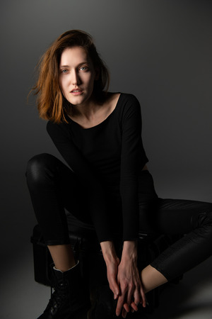Fashion model. Young woman posing in studio wearing black with boots. Beautiful caucasian girl over gray background Stock Photo