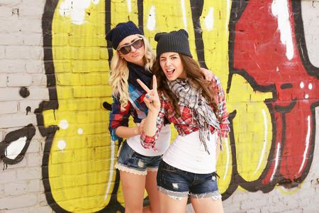 Young pretty hipster girls having fun outdoor, summer on the street. Teenage lifestyle. Trendy modern portrait of funny beautiful teen girls over grunge wall. Two young women have fun together