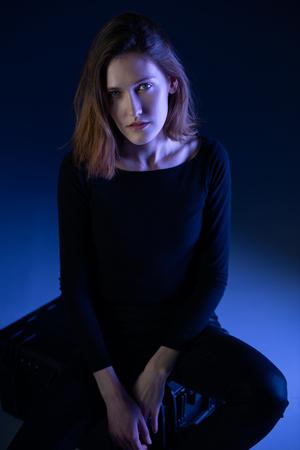 Fashion model. Portrait of young woman posing in studio with blue light. Beautiful caucasian girl Stock Photo - 122781746