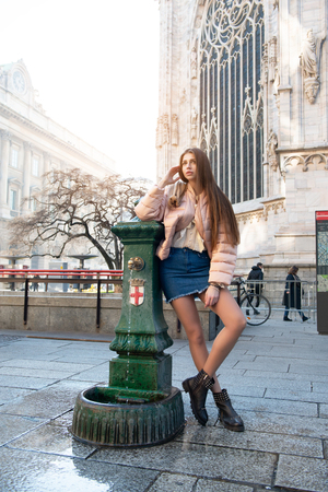 Young attractive woman posing near drinking fountain over Milan Cathedral (Duomo di Milano), Italy. Beautiful girl walking Milanese streets