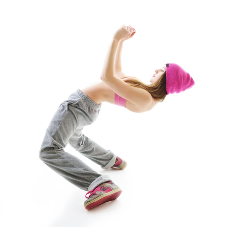 Full-length portrait of carefree girl in gray pants, pink top and hat jumping and dancing. Teen girl hip-hop dancer, over white background. Stock Photo