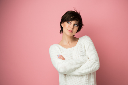 Beautiful young female posing at studio over pink background looking right at copyspace. Pretty brunette woman portrait. Girl thinks, dreams, makes plans for the future Stock Photo