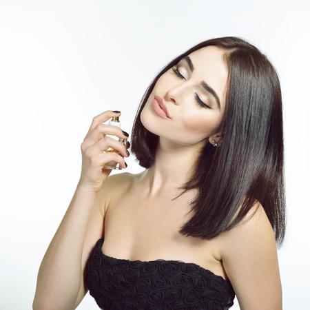 Mädchen mit Parfüm, junge schöne Frau, die eine Flasche Parfüm hält und Aroma riecht. Hübsche Dame, die mit einer Flasche teurem Parfüm aufwirft. Standard-Bild